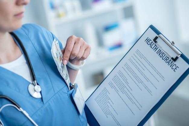 Frau in einem laborkittel, der einen krankenversicherungsvertrag hält und dollar in die tasche steckt