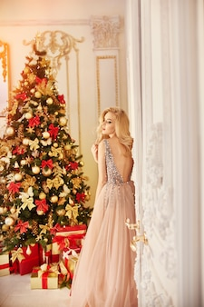 Frau in einem langen cremefarbenen kleid, stehend nahe dem weihnachtsbaum