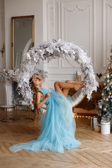 Frau in einem langen kleid auf einer schaukel am weihnachtsbaum