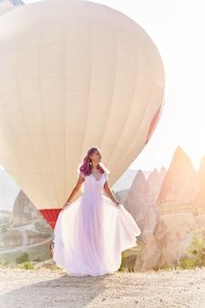 Frau in einem langen kleid auf hintergrund von ballonen in cappadocia