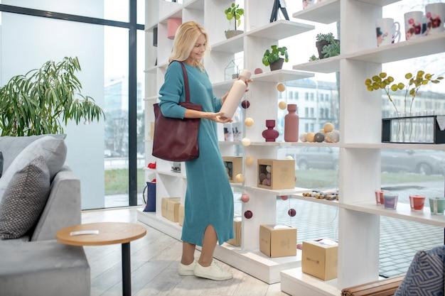 Frau in einem langen kleid und mokassins, die vor dem gestell in einem hellen raum mit einer weißen vase in ihren händen stehen, freudig.