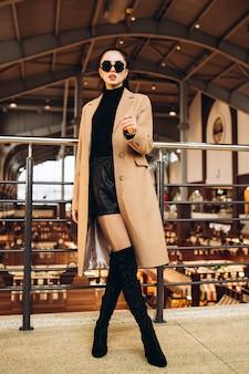 Frau in einem leichten wollmantel und langen stiefeln