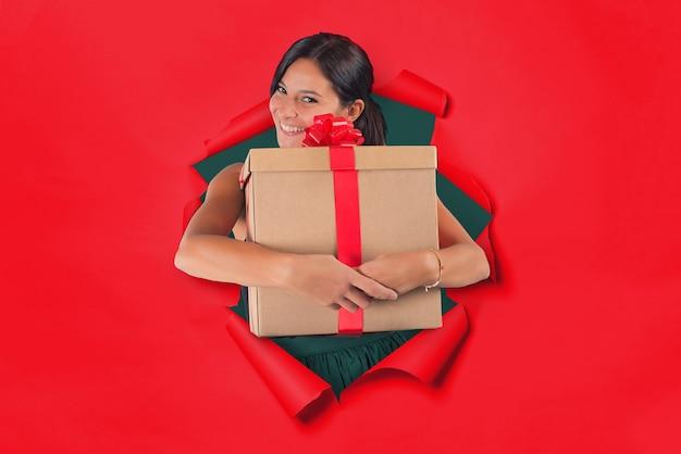 Frau in einem loch auf rotem papierhintergrund hält ein geschenkpaket fest in ihren armen