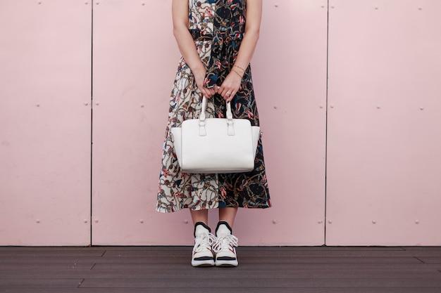 Frau in einem modischen kleid mit einer weißen stilvollen tasche stehen nahe der rosa wand. damenmode sneakers