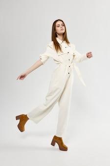 Frau in einem modischen overall und stiefeln mit absätzen auf einem hellen hintergrund in vollem wachstum