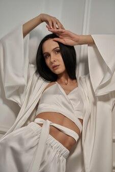 Frau in einem modischen seiden-outfit mit einer wunderschönen frisur und natürlichem make-up seidennachtwäsche