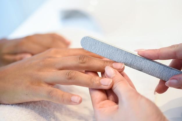 Frau in einem nagelsalon, der eine maniküre mit nagelfeile empfängt