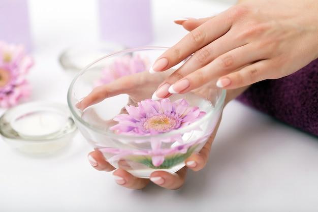 Frau in einem nagelsalon, der eine maniküre von einem kosmetiker empfängt