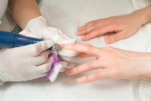 Frau in einem nagelstudio, die eine maniküre von einer kosmetikerin mit nagelfeileschönheit und handpflege erhält
