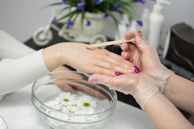 Frau in einem nagelstudio erhält eine maniküre, sie badet ihre hände in paraffin oder wa