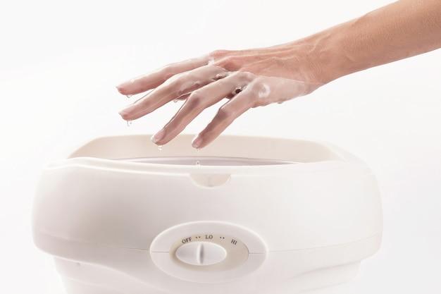 Frau in einem nagelstudio erhält eine maniküre, sie badet ihre hände in paraffin oder wachs