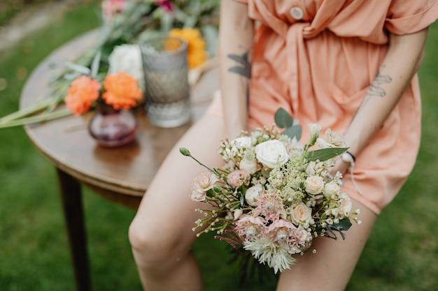Frau in einem orangefarbenen overall mit blumenstrauß
