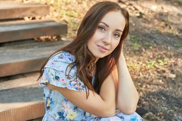 Frau in einem park sitzt auf der treppe