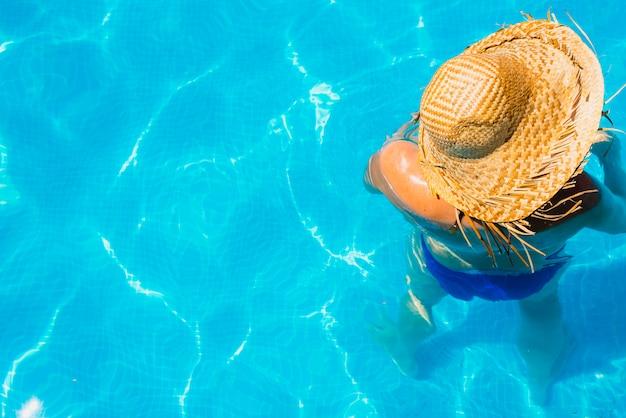 Frau in einem pool mit dem hut entspannte sich und ruhte aus.