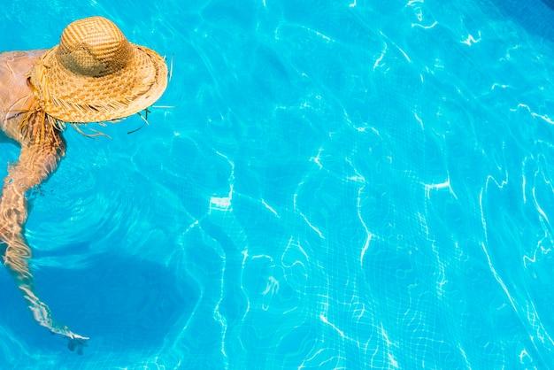 Frau in einem pool mit hut entspannt und ausgeruht.