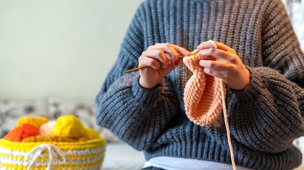 Frau in einem pullover, der auf dem bett mit orangefarbenem garn strickt