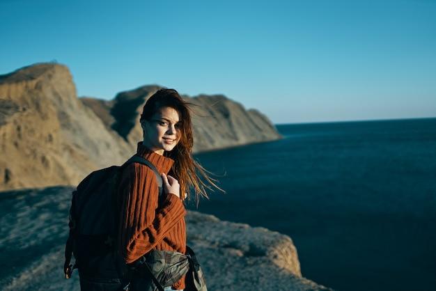 Frau in einem pullover in der natur am meer mit einem rucksack auf dem rücken