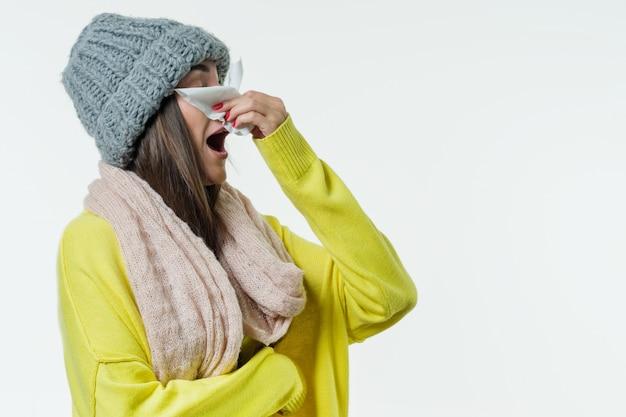 Frau in einem pullover, strickmütze, schal niesen