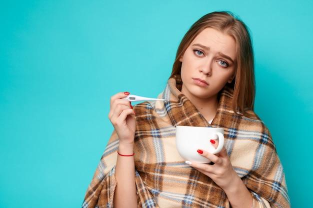 Frau in einem pullover und eine tasse in ihren händen misst die temperatur mit einem thermometer.