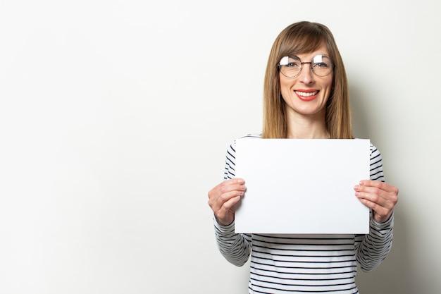 Frau in einem pullover und in den gläsern, die ein leeres blatt papier halten