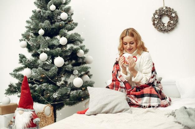 Frau in einem raum. blond in einem weißen pullover. dame in der nähe von weihnachtsbaum.
