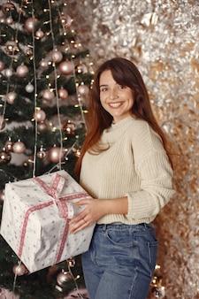 Frau in einem raum. mädchen in einem weißen pullover. dame in der nähe von weihnachtsbaum.