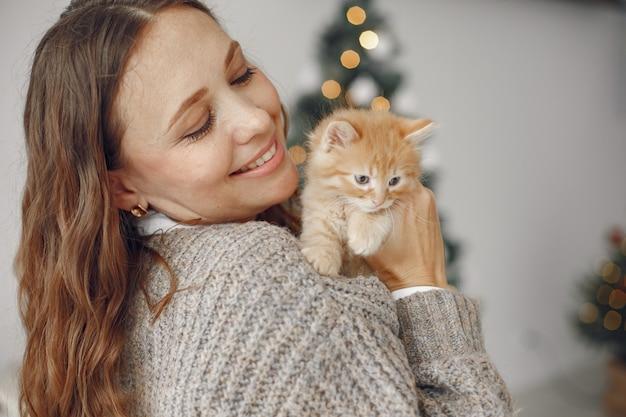 Frau in einem raum. person in einem grauen pullover. dame mit kleiner katze.