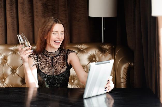 Frau in einem restaurant, das mit glas champagner sich entspannt