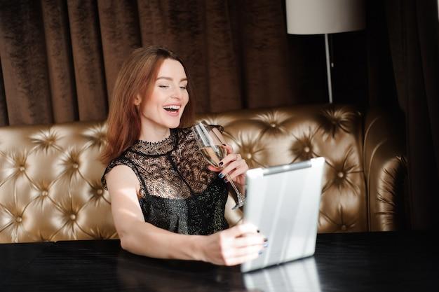 Frau in einem restaurant, das mit glas champagner und tablette pc entspannt.