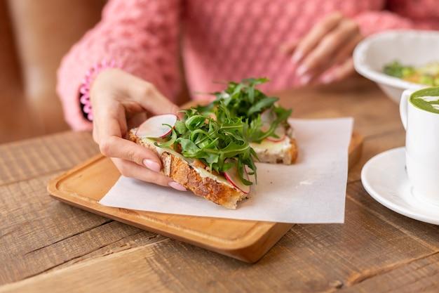 Frau in einem restaurant in einem gemütlichen warmen pullover gesundes frühstück mit toast mit rucola und lachs
