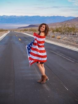 Frau in einem rock geht eine leere straße entlang im tal des todes schwenkt die amerikanische flagge