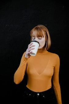Frau in einem rollkragenpullover, die aus einem pappbechermodell zum mitnehmen trinkt