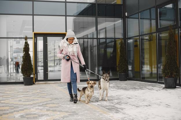 Frau in einem rosa mantel, gehende hunde