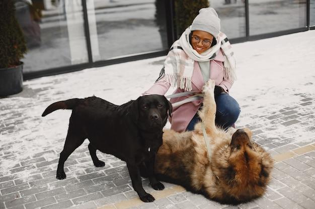 Frau in einem rosa mantel mit hunden