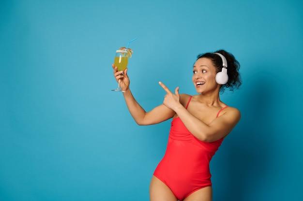 Frau in einem roten badeanzug und kopfhörern, die auf einen cocktail in ihrer hand auf blauem hintergrund zeigen