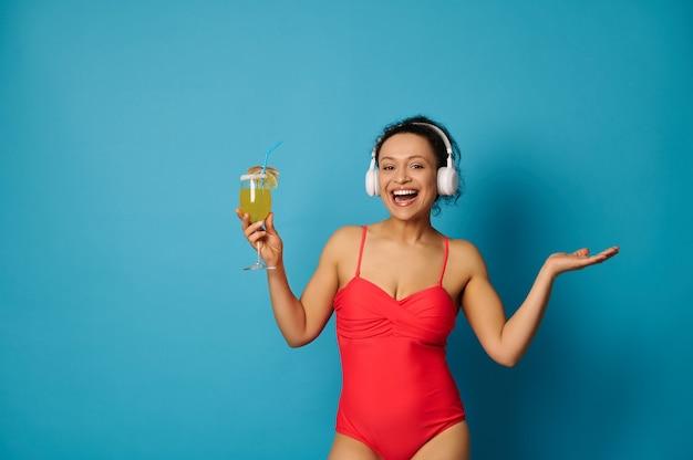 Frau in einem roten badeanzug und kopfhörern, die einen cocktail in der hand auf blauem hintergrund halten