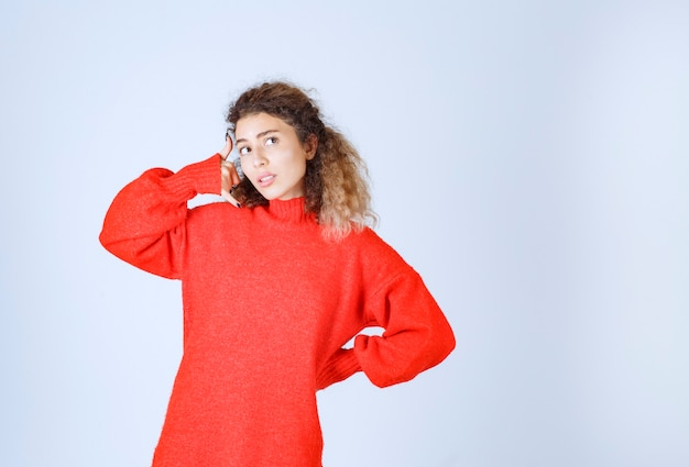 Frau in einem roten hemd, die um einen anruf bittet.