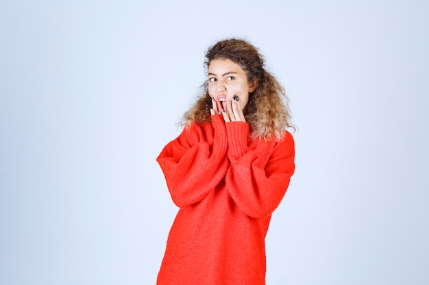 Frau in einem roten hemd sieht pessimistisch oder traurig aus.