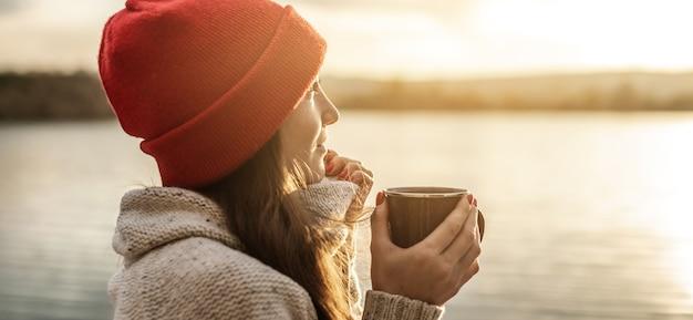 Frau in einem roten hut trinkt kaffee auf dem see bei sonnenuntergang