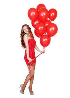 Frau in einem roten kleid mit einem bündel roter luftballons