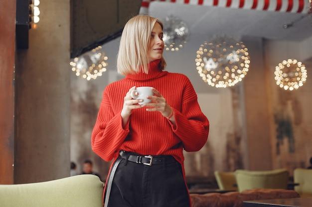 Frau in einem roten pullover. dame trinkt einen kaffee.