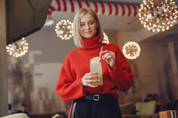 Frau in einem roten pullover. lady trinkt einen cocktail.