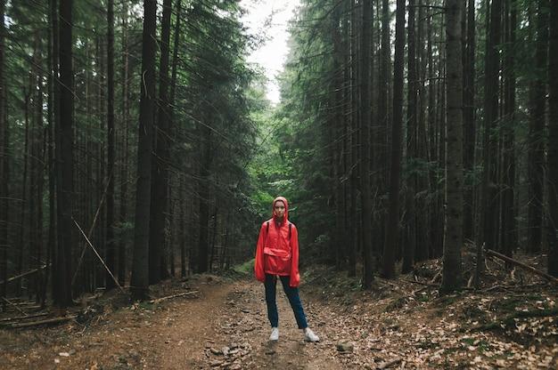 Frau in einem roten regenmantel steht auf einer spur in den bergen