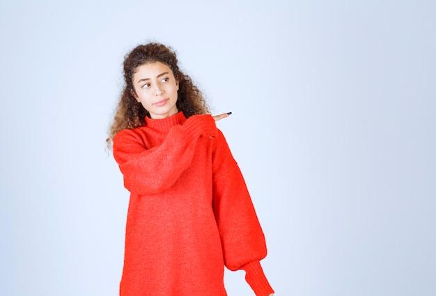 Frau in einem roten sweatshirt, das auf verschiedene seiten zeigt.