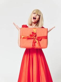 Frau in einem schönen kleid mit geschenkferienboxen im studio, verkauf und feier