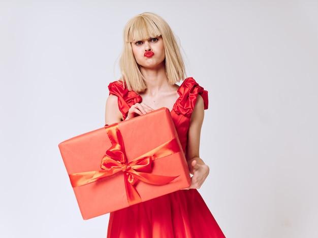 Frau in einem schönen kleid mit geschenkferienkästen, verkauf und feier