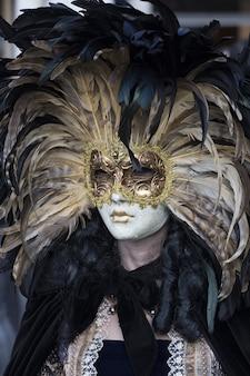 Frau in einem schönen kleid und traditioneller venezianischer maske während des weltberühmten karnevals