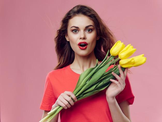 Frau in einem schönen roten kleid mit einer rose und rosenblättern
