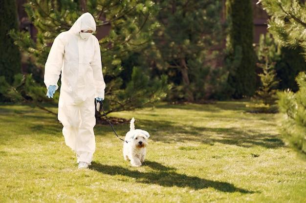 Frau in einem schutzanzug, der mit einem hund geht