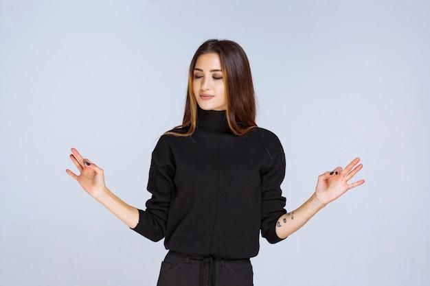 Frau in einem schwarzen hemd, das genusszeichen zeigt.
